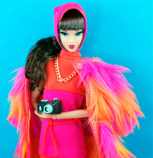 Barbie doll wearing a bright pink and orange coat