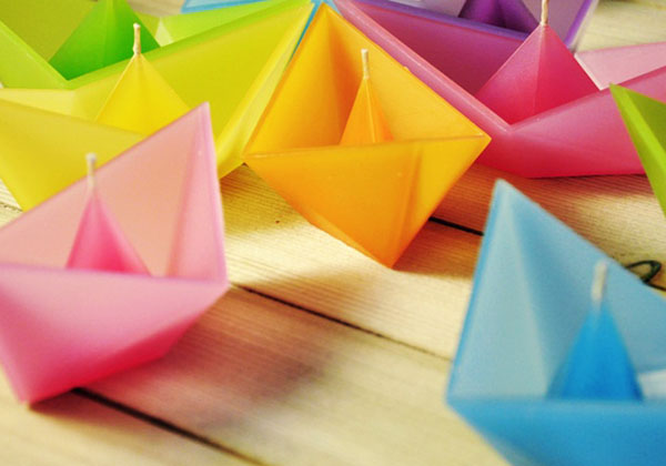 Multicolored folded paper boat candles by Designer Roman Ficek
